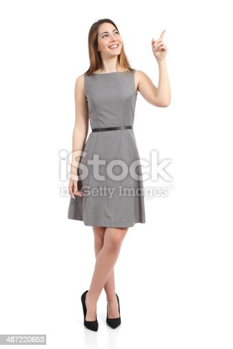istock Full body of a standing woman pointing at side 487220653