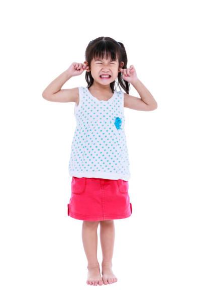 Full body of child putting finger on her ears. stock photo