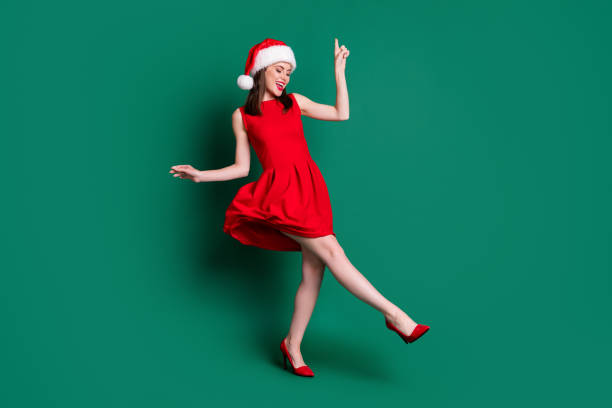 Full body photo of cute attractive lady newyear party festive good mood dancing discotheque youth popular song wear santa cap red mini dress costume stilettos isolated green color background stock photo