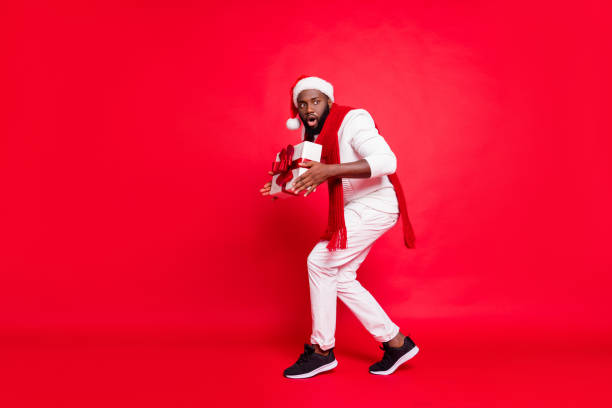 full body photo of dark skin man making newyear surprise for family going tiptoe carry giftbox under x-mas tree wear sweater trousers santa hat isolated red background - santa claus tiptoeing foto e immagini stock