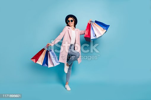 istock Full body photo of enthusiastic candid lady in eyewear eyeglasses go shopping buy purchases wear pink coat denim jeans isolated over blue background 1171895601