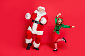 istock Full body photo of excited two santa claus in hat headwear dancing on festive event  wearing green bright costume isolated over red background 1177018330