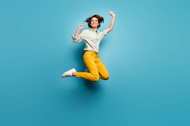Full body photo of funky pretty lady jumping high up celebrating weekend vacation start wear casual green shirt yellow pants sneakers isolated blue color background stock photo