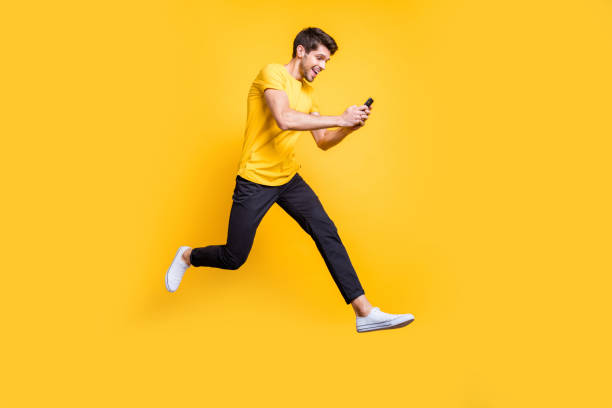 Full body photo of handsome guy jumping high holding telephone rushing romantic date typing girlfriend sms wear casual t-shirt trousers isolated yellow color background Full body photo of handsome guy jumping high holding telephone, rushing romantic date typing girlfriend sms wear casual t-shirt trousers isolated yellow color background mid air stock pictures, royalty-free photos & images
