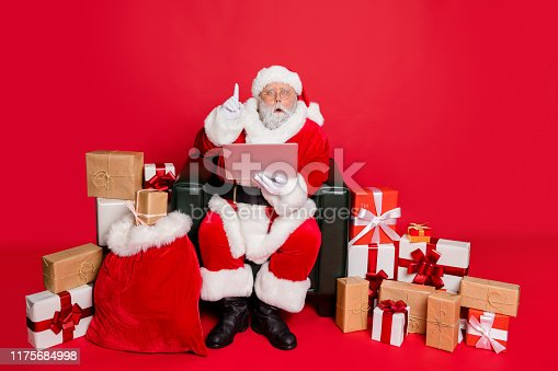 Full body photo of impressed santa claus with eyewear eyeglasses, spectacles use device have genius thoughts wearing headwear hat belt isolated over red background