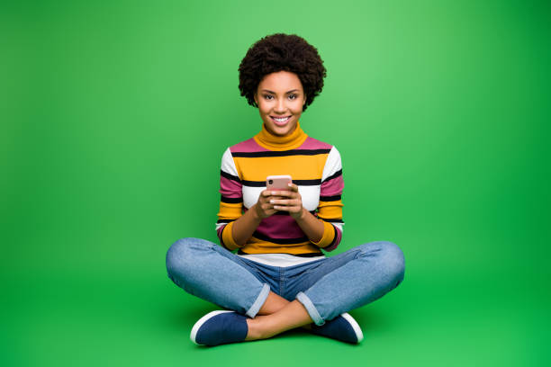 Full body photo of positive afro american girl blogger sit legs crossed folded use smart phone read social network news chill chat wear shine outfit isolated green color background stock photo