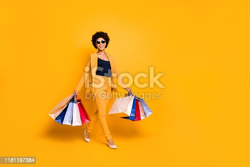 istock Full body photo of positive cheerful afro american girl on travel trip go shopping found sales discounts hold bags wear vogue style outfit sunglass pants high-heels isolated yellow color background 1181197384