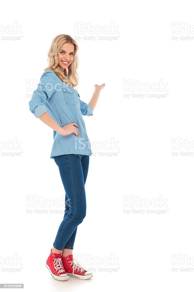 full body picture of a smiling young casual woman presenting - Photo
