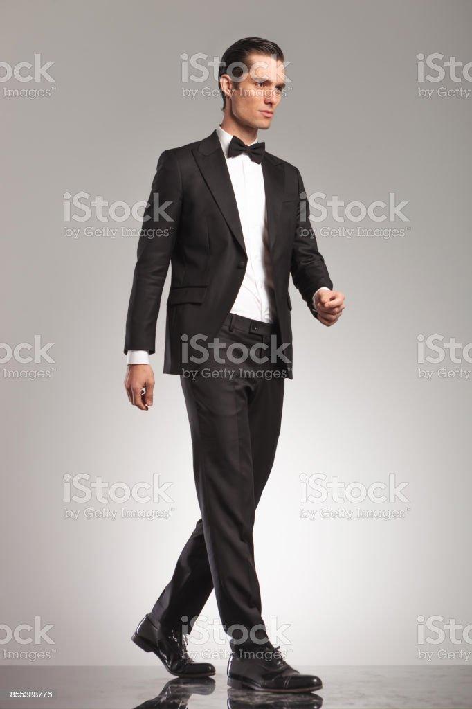 Foto de cuerpo entero de un hombre elegante de smoking caminando foto de  stock libre de 4dc90eb3a8f
