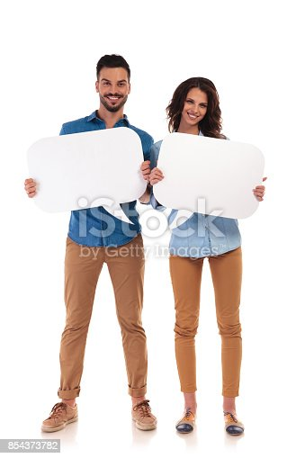 854381780istockphoto full body picture of couple smiling and holding speech bubbles 854373782