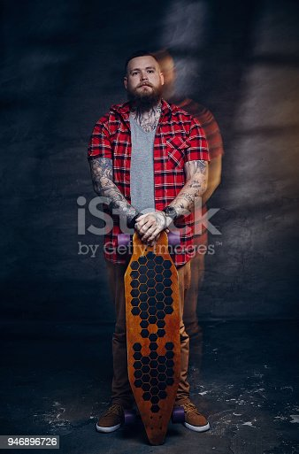 istock Full body portrait of bearded skateboarder with longboard. 946896726