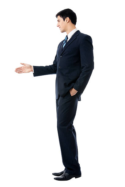Full body portrait of businessman giving hand for handshake stock photo