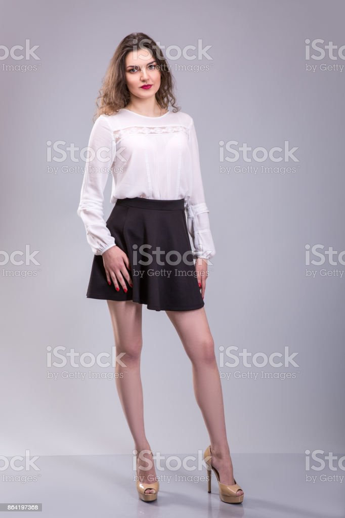 Full body portrait of young woman. Dressed in white top and black skirt beautiful woman stands over Gray background. royalty-free stock photo