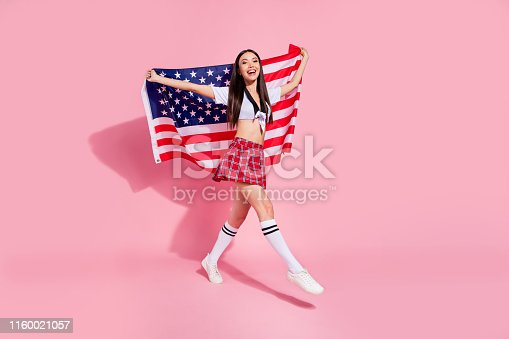 istock Full body profile photo of pretty lady carry usa flag college university english marsh wear white top short plaid skirt isolated pink background 1160021057