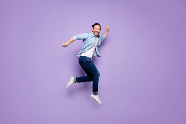Ganzkörper-Profil Seite Foto von verrückten fröhlichen Mann springen haben Ruhe relax run nach frühling Zeit Verkaufsrabatte tragen gut aussehende Kleidung isoliert über violetten Farbhintergrund – Foto