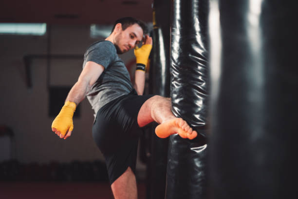 Full body shoot of martial arts trainer giving a leg punch to a punching bag stock photo