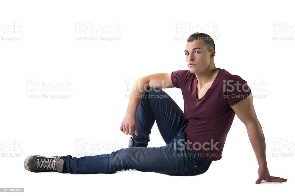Full body shot of handsome young man sitting on floor royalty-free stock photo