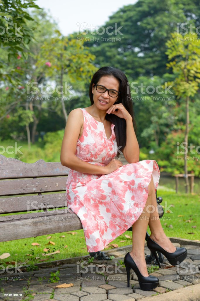 Full body shot of happy Asian woman smiling with head resting on arm while sitting on the bench in nature park stock photo