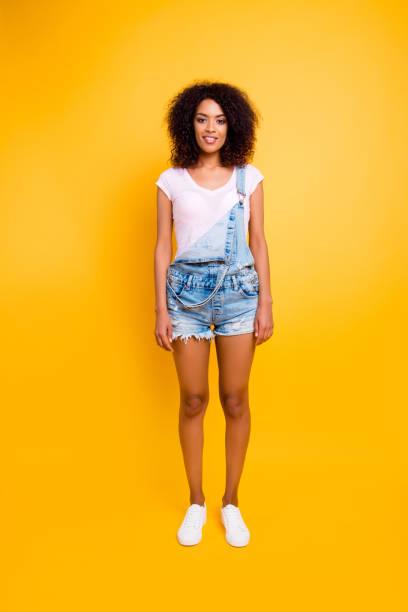 ganzkörper-schuss ziemlich charmante mädchen in weißen t-shirt jeans overall mit schlanken beinen, blick in die kamera auf gelbem hintergrund isoliert - jeans overall stock-fotos und bilder