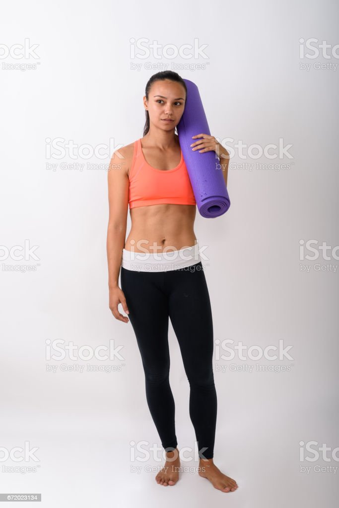 Full body shot of young Asian woman standing and thinking while holding yoga mat ready for gym against white background stock photo
