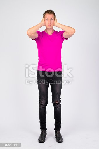 Studio shot of young handsome man wearing purple shirt against white background
