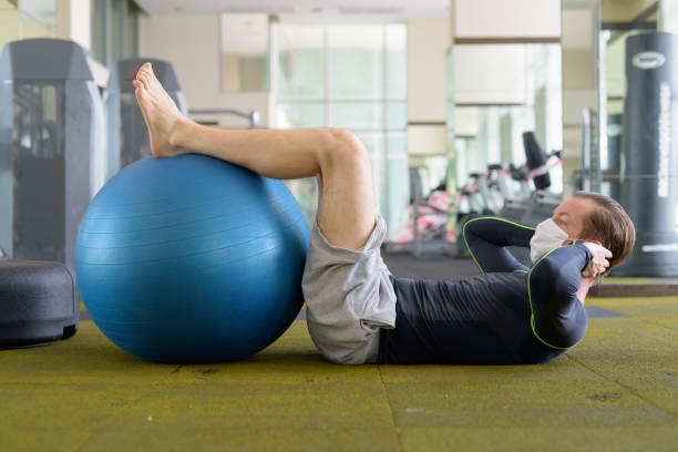 Full body shot of young man with mask doing sit ups with exercise ball at gym during corona virus covid-19 stock photo