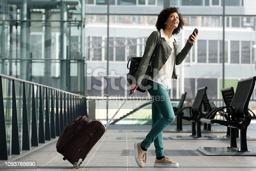 Full body side portrait of travel woman walking at station with suitcase and  cellphone