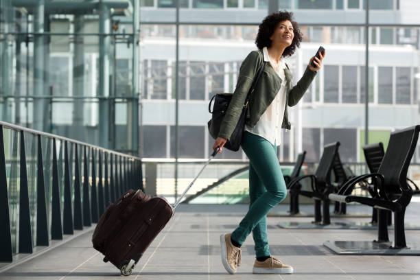 Full body side of travel woman walking at station with suitcase and  cellphone Full body side portrait of travel woman walking at station with suitcase and  cellphone airport stock pictures, royalty-free photos & images