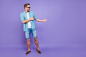 Full body size length of attractive bearded trendy stylish confident cheerful man, wearing denim and glasses, pointing with fingers aside, over bright violet purple background, empty blank copy space
