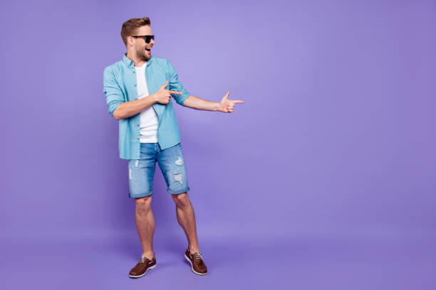 Full body size length of attractive bearded trendy stylish confident cheerful man, wearing denim and glasses, pointing with fingers aside, over bright violet purple background, empty blank copy space Full body size length of attractive bearded trendy stylish confident cheerful man, wearing denim and glasses, pointing with fingers aside, over bright violet purple background, empty blank copy space shorts stock pictures, royalty-free photos & images