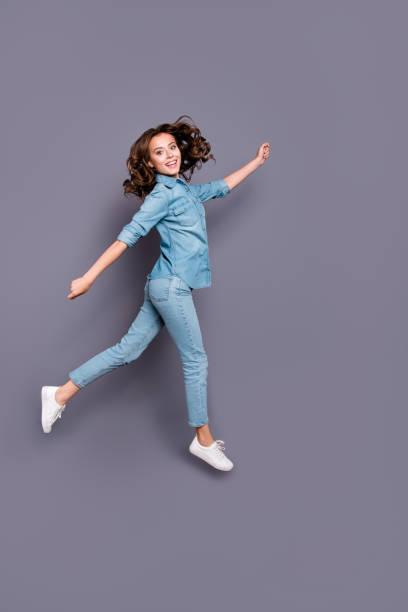 volle größe körperlänge von schön verrückt stilvolle fröhlich attraktive entzückenden mädchen mit lockigem haar in lässigen denim-bluse und jeans, geht in luft, narren, isoliert auf grauem hintergrund - druck jeans stock-fotos und bilder