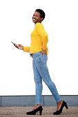 istock Full body young african american woman walking with mobile phone by white wall 1141744186