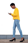 istock Full body young black woman walking with mobile phone by white wall 1141744175