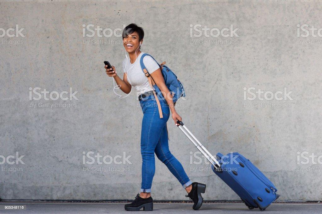 Jeune femme pleine de corps, marchant avec sac de transport et de la téléphonie mobile - Photo