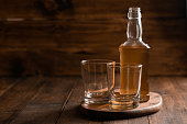 A full bottle of whiskey with empty glasses on a wooden background.