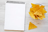 istock Full bowl of nachos and blank notepad on white wooden table, overhead view. Mexican food. Space for text. 1025620740