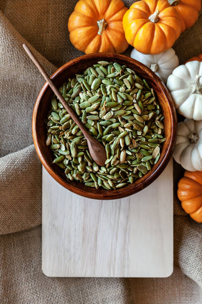 Full bowl of pumpkin seeds closeup on a cutting board with colorful pumpking around stock photo