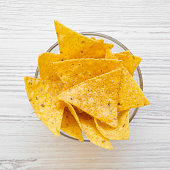 istock Full bowl of tortilla chips on white wooden background, top view. Mexican food. 1020181794