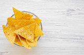 istock Full bowl of tortilla chips on white wooden background, top view. Mexican food. Copy space. 1025618556