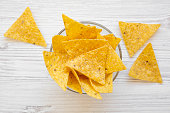 istock Full bowl of tortilla chips on white wooden surface, top view. Mexican food. 1020181806