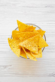 istock Full bowl of tortilla chips on white wooden table, top view. Mexican food. 1025618516