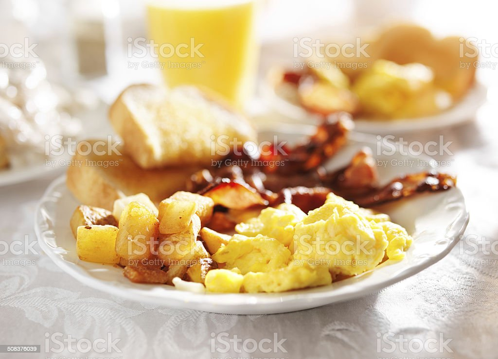 full breakfast with scrambled eggs, fried potatoes and bacon, stock photo