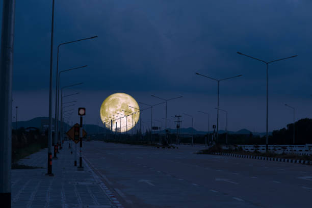 full cold moon back on silhouette power electric pole of seaport on the highway road stock photo