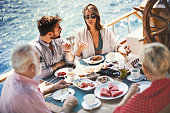 Family having breakfast on the sailing boat. They are eating and talking and enjoying the atmosphere that sea provides.
