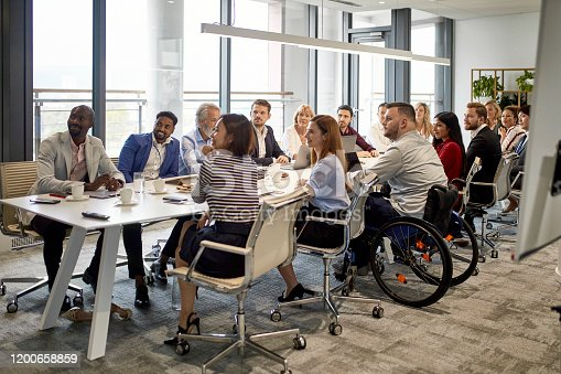 Comprehensive viewpoint of diverse group of business executives sitting together at conference table and looking at camera.