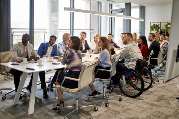 Full Complement of Executives at Management Meeting Comprehensive viewpoint of diverse group of business executives sitting together at conference table and looking at camera. multi ethnic group stock pictures, royalty-free photos & images