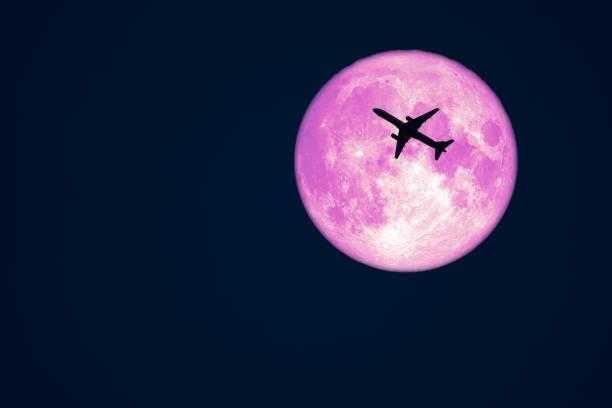 Full Crow Moon and silhouette airplane flight on night sky stock photo