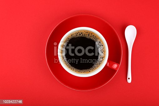 Close up one full cup of black Americano coffee and saucer with white spoon over vivid red paper background, elevated top view, directly above