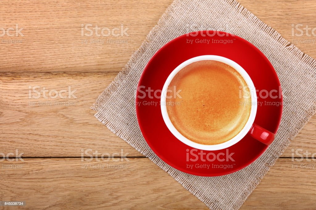 Full cup of espresso coffee in red cup on table stock photo