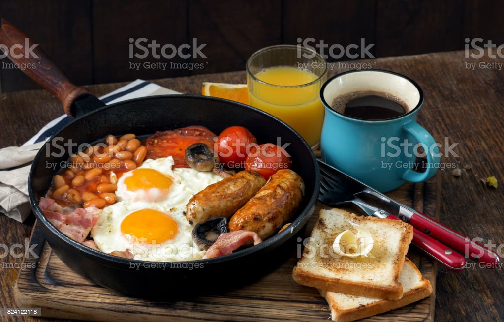 Full English breakfast on wooden table with cup of coffee and orange juice stock photo